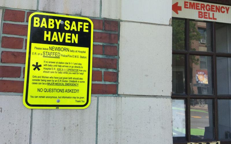 "Photo of Safe Haven sign on Inman Square fire station, and ""emergency bell"" sign to the right."